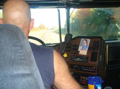 My Truck Driving Husband, doing what he does best! (yea that is me the pic on the dash board)